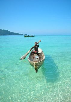 The water is so clear that the boat looks like it's gliding on the surface.