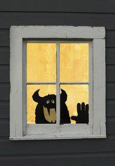 lächelndes Monster am Fensterglas geklebt