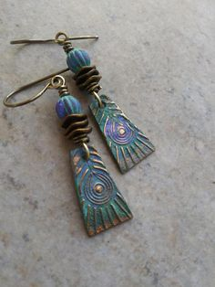 Gorgeous, iridescent peacock feather charms, expertly handcrafted in bronze clay by an etsy artisan, team up with beautiful artisan-made beads with the same finish, as well as brass wavy discs and beads. Wirewrapped with solid brass wire and suspended from solid brass earwires, these