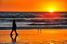 A woman walks on the beach at sunset.