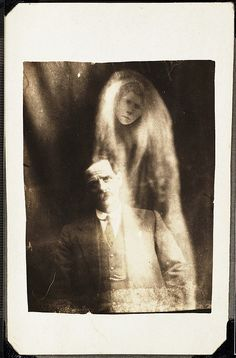 Man with the spirit of his deceased second wife    		A woman's face appears in 'misty' drapes around the man. He was said  to have been asked to sit for a photograph by a voice heard at a  seance held on 6 May 1923. This man had also identified the 'spirit'  of his deceased first wife in an earlier photograph.