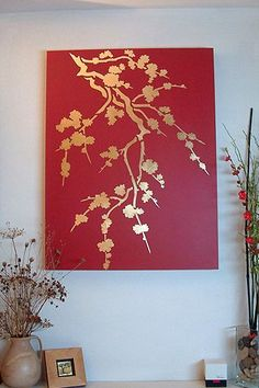 DIY spray paint wall painting.  Spray the canvas gold, place branches and leaves, spray red, let dry.