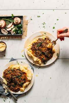 Two serving plates loaded with comforting vegan mashed potatoes topped with super hearty Lentil Mushroom Stew