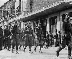 Ένοπλα τμήματα του ΕΛΑΣ μπαίνουν τραγουδώντας στην απελευθερωμένη Λάρισα, στις 23 Οκτωβρίου 1944.