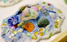 Summer art for kids to create with beautifully colored shells. Children can have lots of fun with different textures as they sculpt and create.