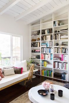 Crisp white walls and vaulted, exposed ceilings are the perfect framework for built-in shelving lined with stacks of colorful books.