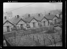 Row of identical houses off Eastern Avenue, in Cincinnati, Ohio, showing backyard outhouses. Ohio River Valley is in the distance | Library of Congress
