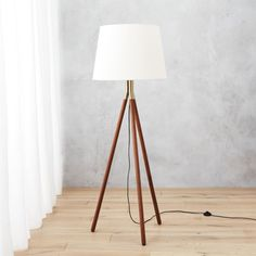 Shop tres floor lamp.   Classic silhouette shines anew.  Tripod legs in warm rubberwood come together in a gleam of gold.  We love how the metal glams up the wood––just enough.  Warm, white linen shade diffuses light down and around for a soft glow.