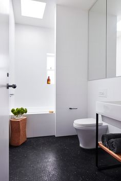 Bathroom: large white wall tiles, black hexagon mosaic floor tiles, window in shower over bathtub, skylight, recessed built-in mirror cabinets