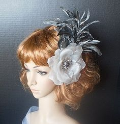 Silver Flower  Fascinator Adorned With Silver Goose Biot Feathers Which are Adorned With Crystals,Silver Coque Feathers and A Crystal and Grey Cabochon Center.