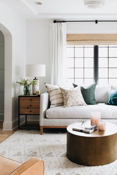 white walls with contrasting black windows. mixing metal and wood furniture and round and rectangular pieces.