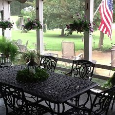 Screened in back porch i love this idea with the iron table and chairs and esp the plants hanging down from the inside