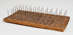"""Lot 29: Pill Dryer - SOLD: $200 - Estimate: $500 – $700 - - - Pine, steel needles, 12 rows of six needles, small medicine balls were rolled round and stacked on each spike for drying, 12 1/2"""" x 6 3/4""""; - labeled """"Pill Dryer Shaker six dozen laxative pills…"""", Shaker pill history by Howard on back, (Flo and Howard Fertig collection)."""