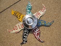 This is hanging on my fence... old license plates with an old hubcap center in the middle, love it!