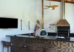 Revestido com mosaico de pastilhas de vidro em tons terrosos, o espaço gourmet conta com churrasqueira, forno a lenha e bancadas em granito preto. Entre o balcão e a mesa redonda lateral, cerca de 10 pessoas podem ser acomodadas para as refeições servidas ao ar livre.