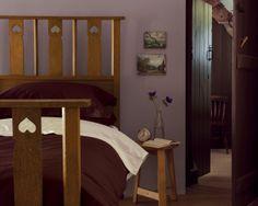 Jouez la nostalgie avec un violet mat. Le violet mat des murs de cette chambre très cosy la réchauffent et s'harmonise avec le bois du lit de campagne à l'ancienne et le parquet.