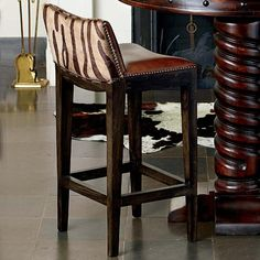 """Built over a sturdy hardwood oak frame this solid brown leather barstool with contrasting brown zebra printed seat back and antique nailhead edging is sure to add a bit of fun to any entertainment area. 18""""W x 16""""D x 38""""H. Please allow 8-10 weeks for delivery. Made in USA."""