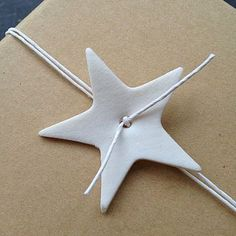 Porcelain star, string tie... Could use foam cut out shapes, or felt (wool like texture) for a more vintage look, or even a cut out from textured cardboard on white wrapping paper!