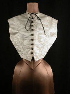 Chemisette, front, circa 1850, white moire, waistcoat shaped and boned laced at back. Black silk buttons, neck trimmed with lace threaded with black velvet ribbon, National Trust Collections.