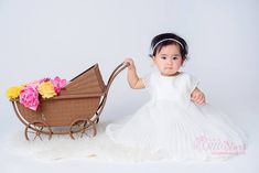 A baby wearing a white dress for a photoshoot. Baby Girl Photography, Children Photography, One Year Old Baby, Baby Prams, Adorable Babies, Doha, Baby Wearing, White Dress, Flower Girl Dresses