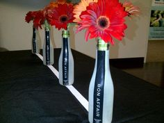 Used Gerbera Red Daisies for the MINI Wine bottles for this centerpiece super easy...Theme is Botox Wine Tasting Party.. Used also a simple Black Table Cloth and just put a white Ribbon down the middle