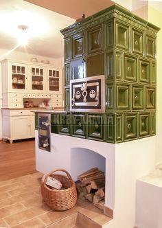 Kachlový sporák s kuchyňským koutem v rekonstruované chalupě. Krásná dřevěná podlaha a v kuchyni použitý starý kredenc. Na kuchyňce ještě chybí dvířka, ale i tak je propojení stavěné části kuchyně se sporákem pěkně sladěné. #kamna #kachlovy #sporak
