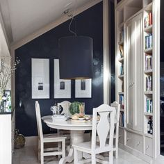 Dark, stenciled wall paper, light furniture, books in the dining nook...what's not to love!