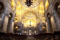 Basilica di San Marco; Venezia; veduta dell'interno.  Osservando l'interno della basilica, è facile trovare elementi appartenenti a diverse comunità, che l'arte romanica tendeva a rispecchiare: il pavimento medievale, la croce d'argento del '700, la luminosità smorzata, tipica bizantina.  L'altare romanico era diviso in una parte superiore, dedicato alla liturgia, e una inferiore, la cripta. Inoltre, è da sottolineare la presenza del matroneo, una tribuna alta sopra l'ingresso centrale.