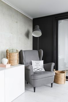 Olohuoneen nurkassa on kiva lepäillä Ikean Strandmon-tuolissa. Tekstityyny on Society6-nettikaupasta. Harsokukka pilkistää Annon korista ja valkoisen omenan Kate on tuonut opiskeluvuoden muistona Japanista. Jalkavalaisin on Ikean Hektar.