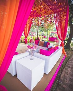 White canopies accentuated with bright pink and orange drapes and some hangings or marigold strings.