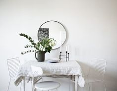 For a small kitchen that doesn't have too much room for a traditional sized dining table, why not opt for a smaller table and add rich décor which will add to your kitchen's stylish design? Adding neutral colored décor like this vase and a rounded mirror are great design ideas for a small kitchen!