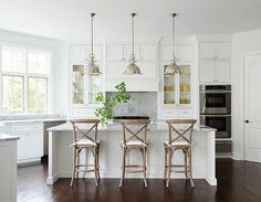 White Kitchen. Classic White Kitchen. White Kitchen kitchen features three Restoration Hardware Harmon Pendants illuminating a white center island topped with gray quartzite lined with three French x back counter stools. A kitchen hood, flanked by glass front cabinets over a gray quartzite backsplash and a stainless steel stove. Kitchen with double wall ovens stacked above a stainless steel warming drawer next to a corner walk in pantry. #Kitchen #WhiteKitchen Shophouse Design.