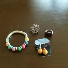 Misc. Jewelry Bracelet with orange, teal, lilac, green, pink, blue, & yellow beads with stretchy band. Mustard colored dangle earrings. Ring with pink stones, antique accents, & stretchy band. Ring with chocolate brown stone & brushed silver extender band. Jewelry