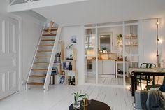 Une petite surface transformée en grands espaces, c'est possible, Une grande hauteur sous plafond, du blanc, et une séparation vitrée forment la base.