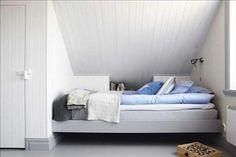 Välinrett under snedtaket. I det blå rummet sover Axel. Sängen är inbyggd och försedd med fiffig bokhylla. Till vänster en inbyggd garderob.