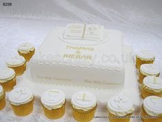 Square first holy communion cake in white with sugar scrolls and flowers. Topped with a sugar open book cake topper with message, date and cross. Surrounded with a selection of matching iced book, chalice and cross cupcakes