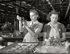 """July 1942. """"Production of aircraft engines at Melrose Park Buick plant near Chicago. Hundreds of gears pass through the expert hands of Dorothy Miller and Sylvia Dreiser during their eight-hour working day in a large Midwest aircraft plant. Inspection of these vital cogs in America's war machine is a delicate task and one which requires infinite patience and precision."""""""