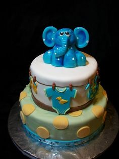Elephant baby shower cake-By The Mad Platters. Love the way they added cute little baby clothes!