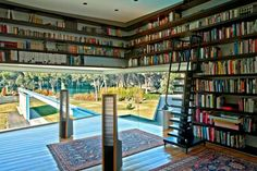 Home library with wraparound shelving and rolling library.