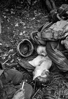 """""""A U.S. Marine listens for the heartbeat of a dying buddy who suffered head wounds when the company's lead platoon was hit with enemy machine gun fire as they pushed through a rice paddy just short of the demilitarized zone in South Vietnam Sept. 17, 1966."""""""