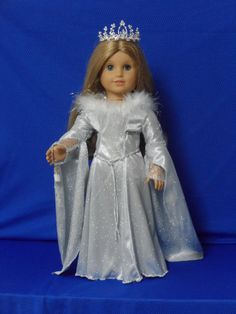 This Winter Princess just loves her glistening gown and wishes for your doll to wear it. She will even give you her magic flask which contains ice crystals.  Sparkly Ice A-line gown for your favorite doll. Edges of the gown is finished with silver thread. The neckline is edged with silver and white marabou feathers. The upper sleeves is adorned with silver design and edged with silver trim. The long trailing sleeves are lined with fine silver mesh which adds that touch of mystic feeling.  A…