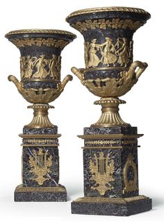 A PAIR OF FRENCH ORMOLU-MOUNTED MARBLE URNS  SECOND HALF OF THE 19TH CENTURY  In the Empire style, of campana form, each with a band of dancing allegorical figures flanked by loop handles, raised on a marble base fitted with laurel wreaths and lyres, the base enriched with overlapping acanthus leaves