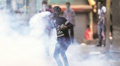 Kashmir. July 2016  A protester hurls an exploded tear gas shell at policemen during a clash in Srinagar on Sunday.