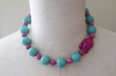 A chunky beaded 16 inch necklace that features 16 mm turquoise howlite beads, accented by a deep rosy pink faceted agate beads in 8 mm, and featuring an asymmetrically placed fuschia Buddha bead. The clasp is a silver plated toggle.This is a quality made necklace, using fine components and made by a skilled and experienced artisan based in the USA.  The necklace will come to you gift boxed and will be shipped quickly.  To see more beaded necklaces, click here…