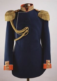 Uniform of Emperor Nicholas II, circa 1896.  The double-breasted coat is of dark-blue woollen cloth with a stand-up collar and cuffs of red cloth; decorated with gold embroidery, epaulettes and aiguillettes. The collar are embroidered in gold thread and spangles with an elaborate pattern; the cuffs bear gilded metal buttons with images of double-headed eagles.  The item is completed with gold epaulettes with the monogram of Tsar Alexander III.
