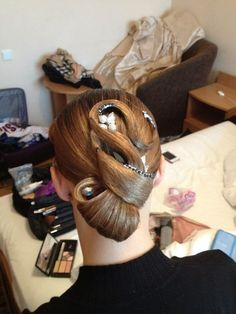 Low looped bun with simple swirls and rhinestone accents. Great hairstyle for latin and standard ballroom. Visit http://ballroomguide.com/comp/hair_make_up.html for more hair and makeup info