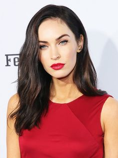 Megan Fox wears a paneled red dress with a red lip at an event