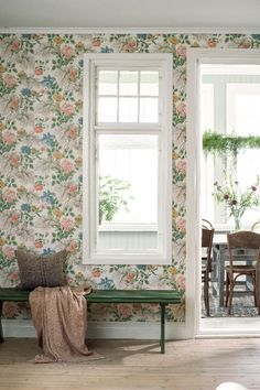 A traditional all over feathery wallpaper floral trail design, with different flowers on the same plant.