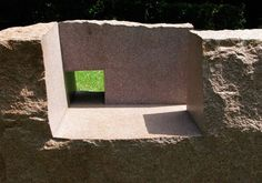 Several Chillida sculptures with excavated cubic architectural volumes and viewing apertures leading to other dimensions appear to explore t...