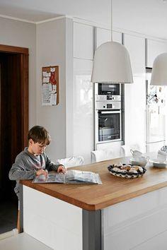 Blat wyspy na co dzień służy jako stół śniadaniowy. Siadają przy nim również chłopcy, by towarzyszyć zajętej gotowaniem mamie. W razie potrzeby bywa też wygodnym miejscem  pracy dobrze oświetlonym przez dwie lampy sufitowe.